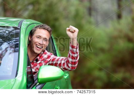 Green energy biofuel electric car driver happy and excited. Man driving new vehicle in cheerful in nature forest. Young male driver looking at camera with arm raised cheering.