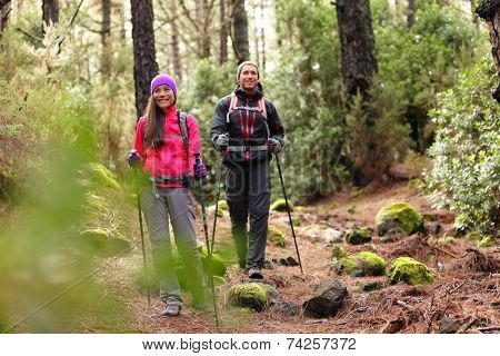 Hiker couple backpackers hiking in forest on path in mountains. Multiracial woman and man living healthy active lifestyle enjoying nature in La Esperanza forest, Tenerife, Canary Islands, Spain.