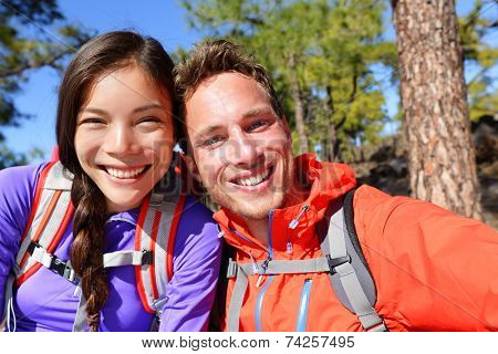 Selfie couple taking self-portrait hiking using smart phone camera in nature. Happy couple taking self-portrait photo picture looking at camera smiling happy. Man and woman having fun together.