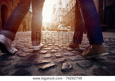 tourist couple walking on cobblestone street vacation in europe on holiday break