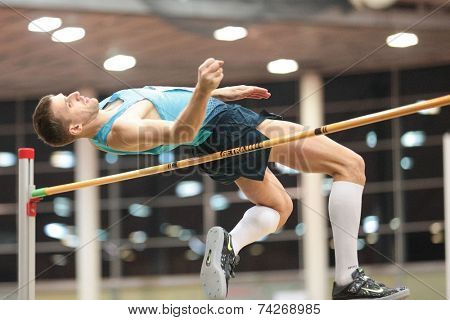 LINZ, AUSTRIA - JANUARY 30, 2014: Aleksey Dmitrik (#509 Russia) wins the men's high jump event in an indoor track and field meeting.