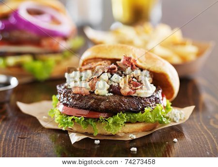 gourmet burgers on wooden table with bleu cheese and bacon