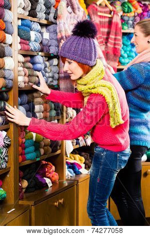 Young women buying colorful wool and yarn for their hobby in a knitting shop