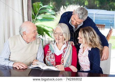 Happy couple looking at grandparents reading book while sitting in nursing home