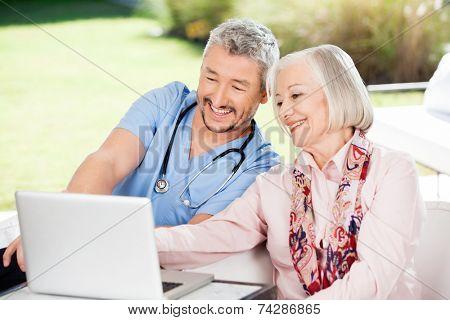 Happy caretaker and senior woman using laptop at nursing home porch