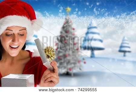Smiling woman opening christmas present against blurry christmas scene poster