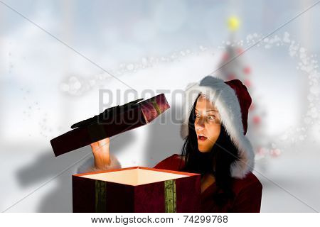 Surprised woman opening christmas present against blurry christmas tree in room poster