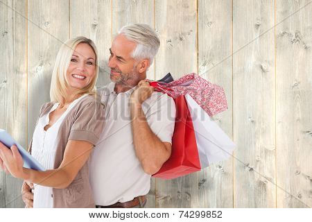 Happy couple with shopping bags and tablet pc against pale wooden planks poster