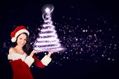 Pretty girl presenting in santa outfit against glowing christmas tree poster