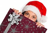 Woman looking towards the camera against christmas wrapping paper with bow poster