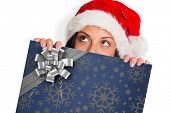 Woman looking away from camera against christmas wrapping paper with bow poster