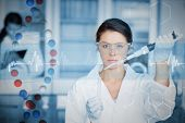 Serious chemist working with large pipette and test tube against dna helix in blue and red with ecg line poster