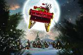 Santa flying his sleigh against christmas village under full moon poster