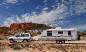 Four wheel drive and large offroad caravan ( RV ) in outback Australia against a stunning red rock outcrop with an deep blue sky and interesting cloud formations poster