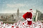 Santa walking on pile of gifts against balcony overlooking city poster
