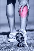 Muscle injury - Man running clutching calf muscle after spraining it while out jogging on the beach. Male athlete sport injury. poster