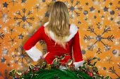 Pretty girl in santa outfit holding gift against snowflake wallpaper pattern poster