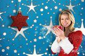 Pretty santa girl holding mug against snowflake wallpaper pattern poster