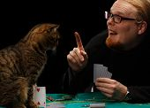 Young smiling red-haired bearded man in glasses holds finger up playing poker with tabby cat sitting at gaming table on black background poster