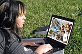 A young woman viewing or editing a gallery of photos on her laptop computer. poster