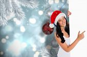 Woman pointing to large sign against baubles hanging over christmas scene poster
