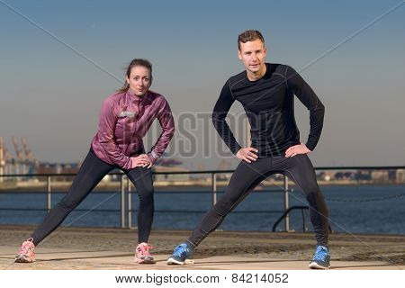 Young Couple Exercising At The Waterfront