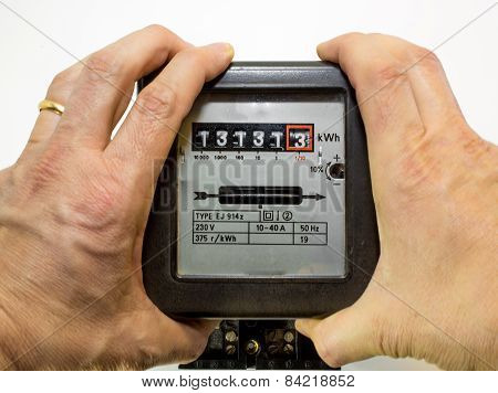 Hands Tightened Around The Electrical Energy Meter