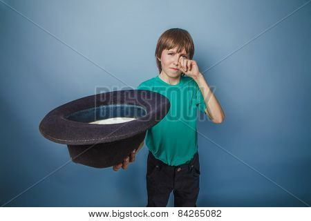 boy teenager European appearance in green t-shirt holding a hat