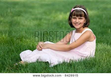 Girl In Pink Resting On The Green Grass