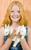 Teen girl with two pet rabbits smiling indoor poster