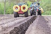 Two agriculture tractors digging drainage pipes in ditch deep in ground poster