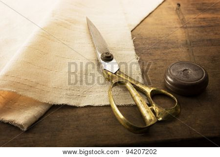 Gold scissors and natural white fabric. Measuring, cutting, sewing textile or fine cloth. Work table of a tailor. Shallow depth of field, Focus on scissors