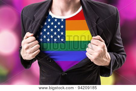 Businessman stretching suit with American LGBT flag on bokeh background