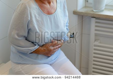 Senior Woman Sitting On Toilet