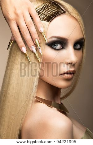Beautiful fashionable girl in a glamorous image with bright makeup and long gold nails. Art design manicure. Picture taken in the studio. poster
