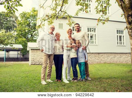 family, happiness, generation, home and people concept - happy family standing in front of house outdoors