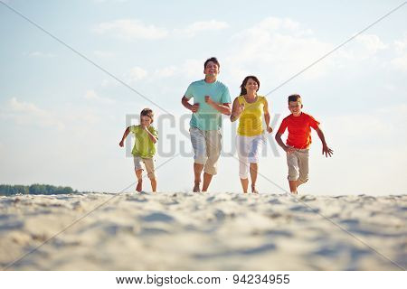Modern family in casualwear running on sandy beach