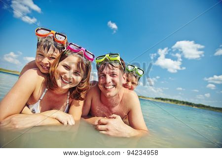 Happy family in goggles looking at camera in water