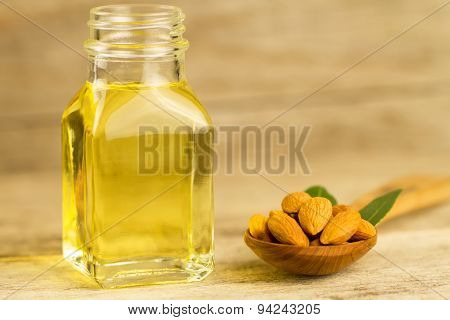 Peeled Almonds In A Spoon And Oil In A Jar On Wooden Background
