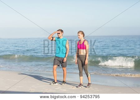 Sporting couple looking far away at the beach