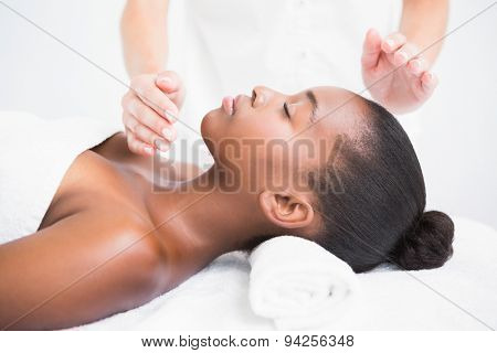 Pretty woman enjoying a reiki technique at the health spa