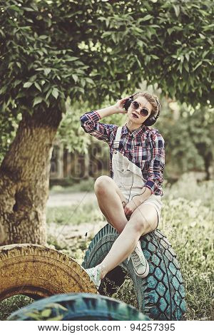 Hipster Girl Listening To Music With Headphones In Summer Park In Shade Of Tree.