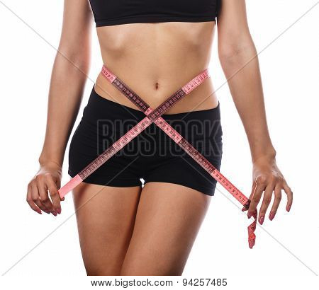 Young slim woman measuring waist circumference following a diet and sports exercises. Isolated on white background. The concept of excess weight loss and healthy eating. poster