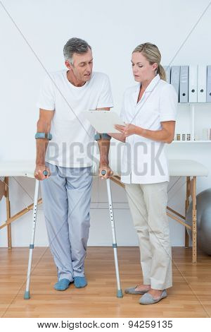 Doctor showing clipboard to her patient with crutch in medical office