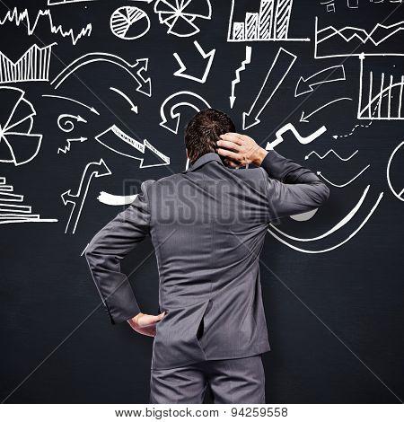 Thinking businessman scratching head against blackboard
