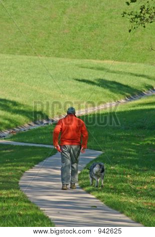 a man with orange coat on walking dog in park poster