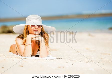 Sexual happy blond girl with sunglasses and white hat take sunbath on the beach enjoying summer holi