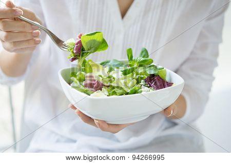 Close up shot of a woman holding a plate of fresh green salad in the beautiful morning light. She's holding a fork and she's about to eat the vegetarian food. Healthy eating and diet concept.