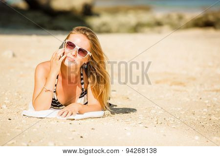 Sexy young blond girl in sunglasses speaking on the phone  enjoying summer holidays. Travel, vacatio