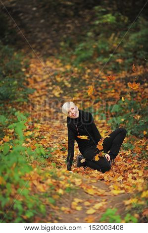 The laughing young girl sitting on her knees on the fallen foliage in the woods, in the air circling the bright maple leaves